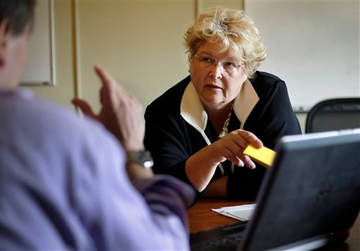 Christine Ferguson, director of the Rhode Island health insurance exchange, takes part in a meeting at the Statehouse in Providence, R.I. The Rhode Island marketplace will postpone a feature that allows consumers to enter the names of their doctors and instantly find out what insurance plans they accept.