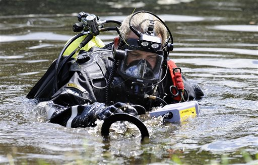 A Connecticut State Police dive team member searches Pine Lake in Bristol, Conn., the hometown of the former New England Patriots player Aaron Hernandez on Monday. Other officers could be seen combing the water's edge.
