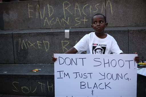 Abdul Kebbeh, 6, holds a sign at Westlake Park on Sunday, July 14, 2013 in downtown Seattle. Hundreds of people gathered at Westlake and marched to the United States Court House to protest the acquittal of George Zimmerman, the Florida man that shot and killed Trayvon Martin.