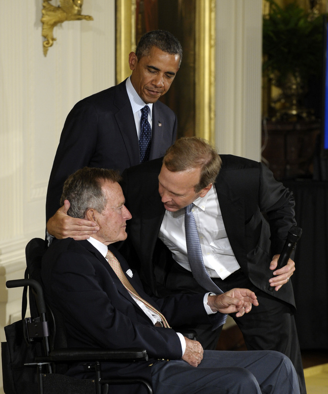President Barack Obama, standing, watches as former President George H. W. Bush, left, gets a hug from his son Neil Bush during a ceremony to recognize the 5,000th Daily Point of Light Award at the White House on Monday.