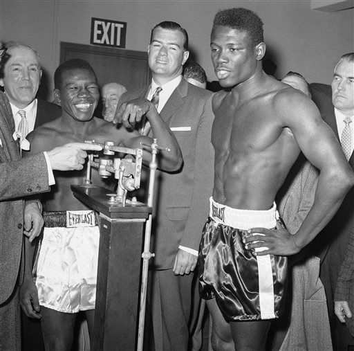 In this March 24, 1962, photo, welterweight champion Benny Paret, in white trunks, reads the weight of challenger and former champion Emile Griffith during the weigh-in for their title fight in New York. In center is James A. Farley, Jr., a member of the New York State Athletic Commission.