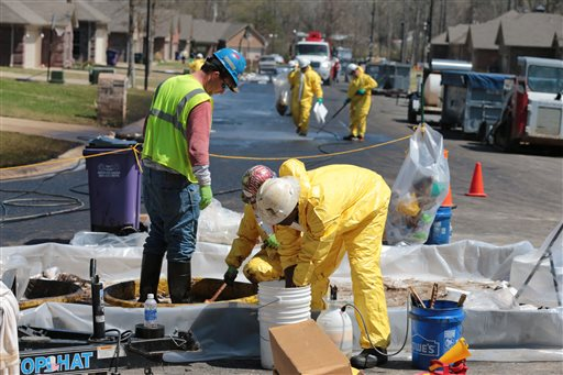 A crew member with Exxon Mobil washes oil from another crew member's boots in a subdivision in Mayflower, Ark., in this April 1, 2013. photo. The leak dumped about 210,000 gallons of heavy oil into the neighborhood.