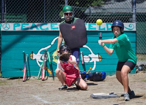 Laila, from Cairo, Egypt, bats during a softball game at the Seeds of Peace camp in Otisfield Friday. The summer camp brings together young people from countries at conflict.