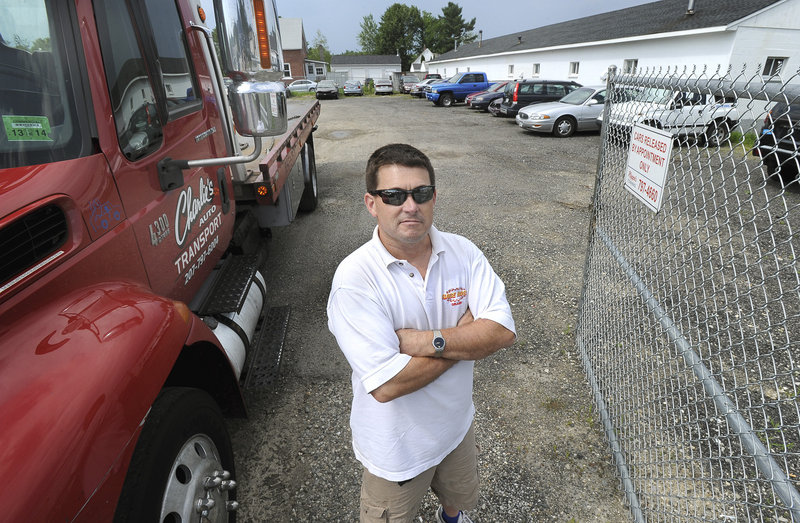Ben Roussel of Charlie's Auto Transport stands by his truck and lot on Warren Avenue in Portland on Thursday, July 18, 2013.