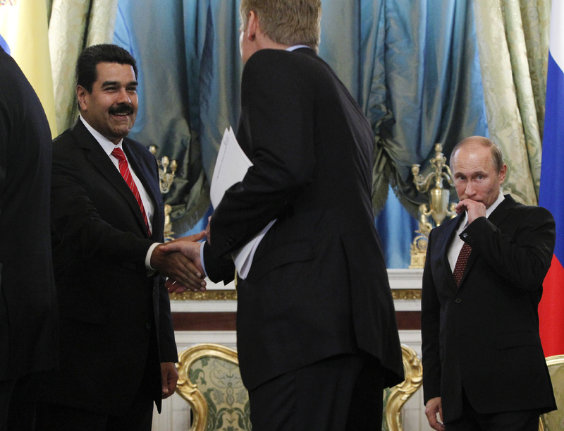 Venezuelan President Nicolas Maduro, left, shakes hands with Russian presidential spokesman Dmitry Peskov on Tuesday during a meeting at the Kremlin in Moscow. At right is Russia's President Vladimir Putin. Maduro has expressed support for Edward Snowden.