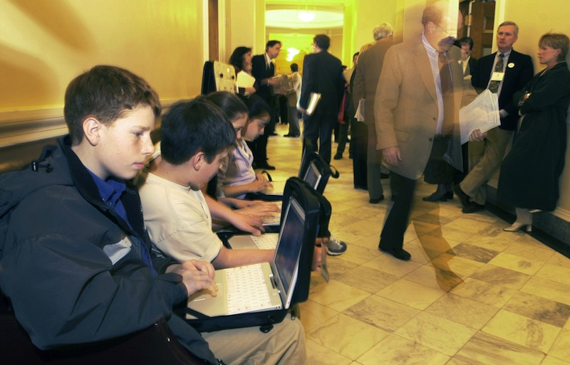 In this 2002 file photo, Shapleigh Middle School seventh-graders use their laptops in the hallway outside the Senate chamber as lawmakers and lobbyists go about business at the Maine State House in Augusta. Maine's