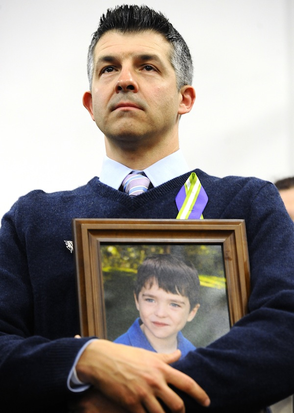 "In this Jan. 14, 2013 file photo, Ian Hockley, father of Sandy Hook School shooting victim Dylan, holds a photo of his son at a news conference at Edmond Town Hall in Newtown, Conn. Some Newtown families have said they were given a voice late in the process of dispersing the millions of dollars in donated funds, and that the process has been bureaucratic, difficult, unpleasant, and has added to their pain. ""What's the objective here?"" Hockley said. ""The objective is to heal Newtown and to take care of its most affected people."" (AP Photo/Jessica Hill, File)"