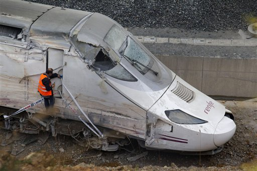 A rail worker checks the cabin of the train that was carrying 218 passengers when it hurtled off the tracks and slammed into a concrete wall. The Spanish rail agency has said the brakes should have been applied 2.5 miles before the train hit the curve.