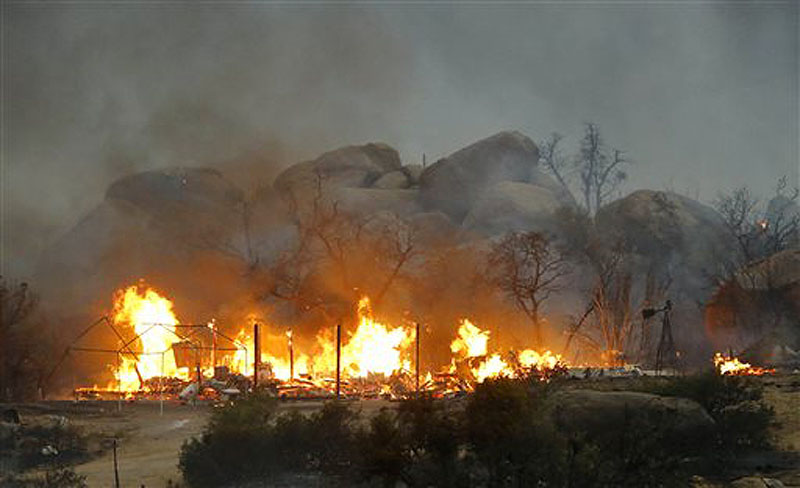 Homes burn as the Yarnell Hill fire burns in Glenn Ilah on Sunday near Yarnell, Ariz. The fire started last Friday and picked up momentum as the area experienced high temperatures, low humidity and windy conditions.