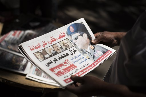 Egyptian man holds a newspaper the news near Mesaha Square, in Cairo , Thursday. The chief justice of Egypt's Supreme Constitutional Court was sworn in Thursday as the nation's interim president, taking over hours after the military ousted the Islamist President Mohammed Morsi. (AP Photo/ Manu Brabo)