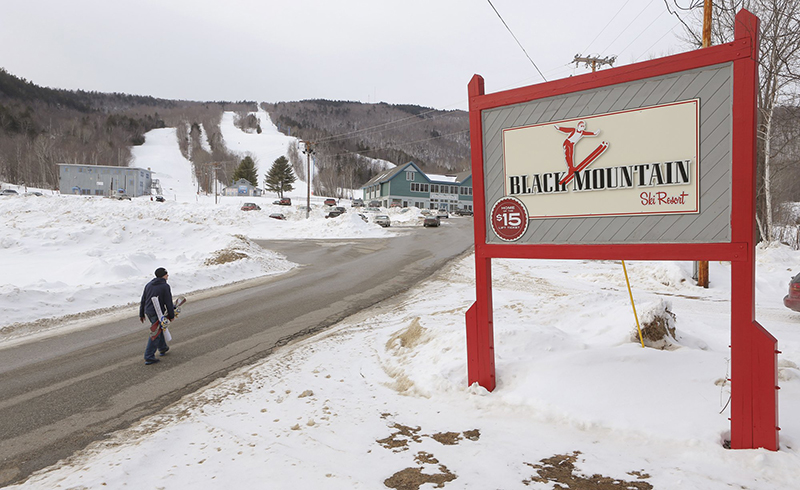 A snowboarder walks up the main access road to Black Mountain in Rumford in January.