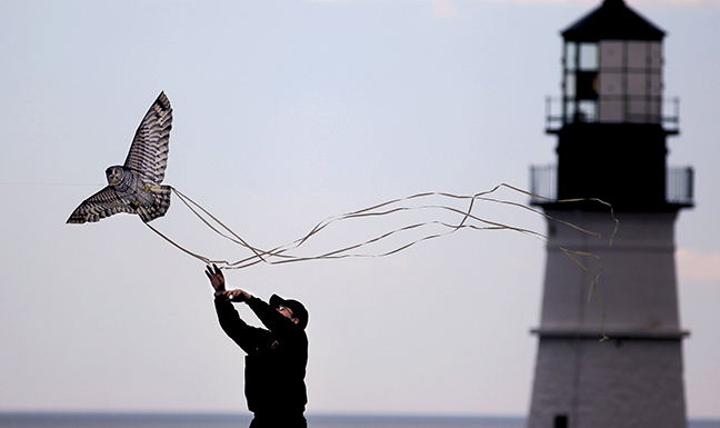 With Portland Head Light in the background, Tyler Romo, 19, of Yarmouth High School, launches a kite the shape of an owl at Fort Williams Park in Cape Elizabeth in this June 4, 2013 file photo. Proposed new rules would allow up to eight art vendors to sell their work at Fort Williams.
