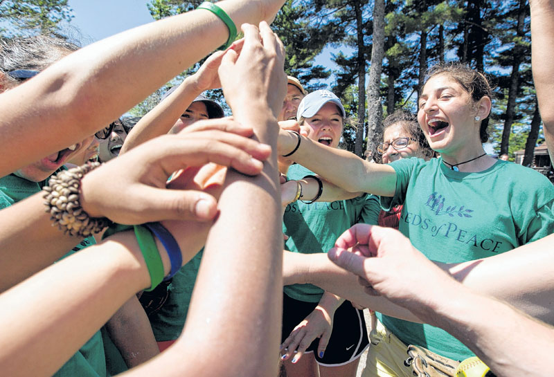 Campers cheer before taking the field for a softball game at the Seeds of Peace camp in Otisfield. The summer camp brings together young people from countries in conflict.