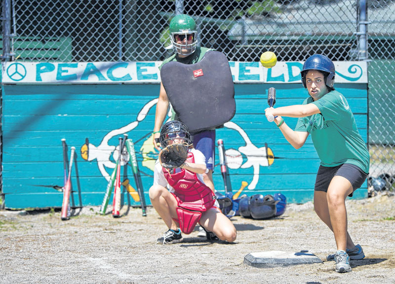 Seeds of Peace camper Laila, right, from Cairo, Egypt, keeps her eyes on the ball during a softball game Friday.