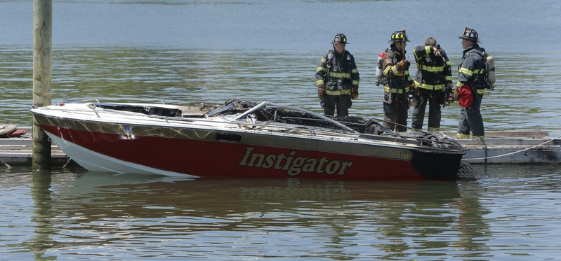 Portland firefighters examine a boat that exploded and caught fire at the boat launch at the Eastern Prom in Portland on Friday.