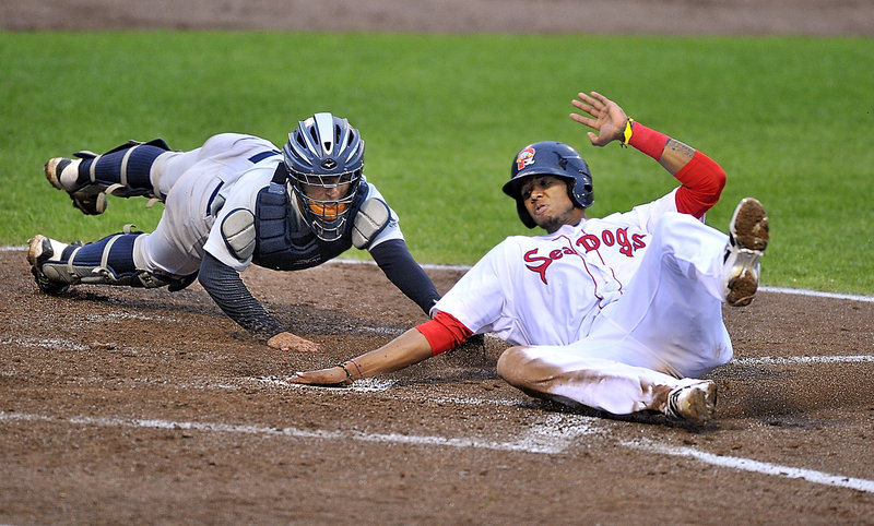 Michael Almanzar of the Portland Sea Dogs slides past Trenton catcher Francisco Arcia to score in the fourth inning of the first game of a doubleheader sweep Tuesday night.