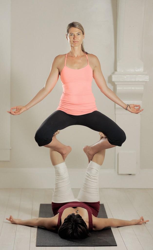 Justine Carlisle, top, and Kara Seymour of Bhakti In Motion do acro yoga at Akari in Portland.