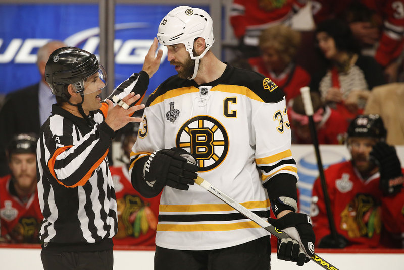 Wes McCauley explains a situation to the Bruins' captain, defenseman Zdeno Chara, during a Stanley Cup finals game in Chicago.