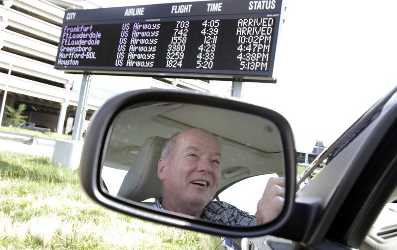 Joe McGuriman of Lansdale, Pa., parks in front of one of three electronic flight status boards at the cellphone lot at Philadelphia International Airport on June 19.