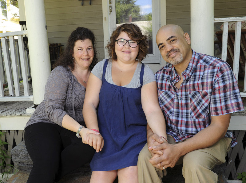 In this June 20, 2013 photo, Becky Bluh, left, and Tony Derricotte pose for a photo with their daughter, Cameron Bluh-Derricotte, center, at their home in Greenfield, Mass. The Make-A-Wish Foundation has arranged a trip to London for Cameron, who has a rare autoimmune disorder. (AP Photo/Greenfield Recorder, Paul Franz)