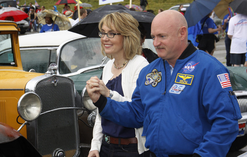 Former U.S. Rep. Gabrielle Giffords and her husband, former astronaut Mark Kelly, walk with supporters to a car as they take part in a parade in Northside, Ohio, on Thursday. Giffords, who was wounded in a mass shooting in 2011, is coming to Maine on Saturday with her husband to discuss gun owners' rights and responsibilities.