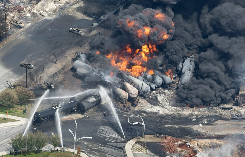 In this July 6 photo, flames and smoke rise from railway cars that were carrying crude oil after derailing in downtown Lac Megantic, Quebec, Canada, devastating the downtown and killing at least 50. (AP Photo/The Canadian Press, Paul Chiasson)