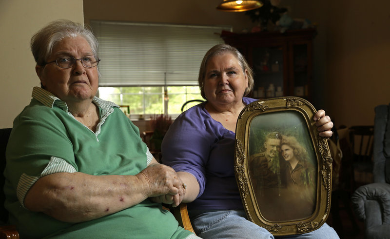 Shelia Reese, right, sits with her mother Chris Tench in Chapel Hill, N.C. Reese is holding a portrait of her mother and her father, Kenneth F. Reese, a soldier who is still listed as MIA – missing in action – from the Korean War.