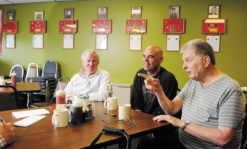 "David Harville, left, Thomas ""T.J."" Quinn, center, and Larry Day talk about the memorial wall display last week at Quinn's restaurant, TJ's Place, in Monmouth. There are seven plaques on the wall, one for each of the soldiers from the town killed in action in World War II."