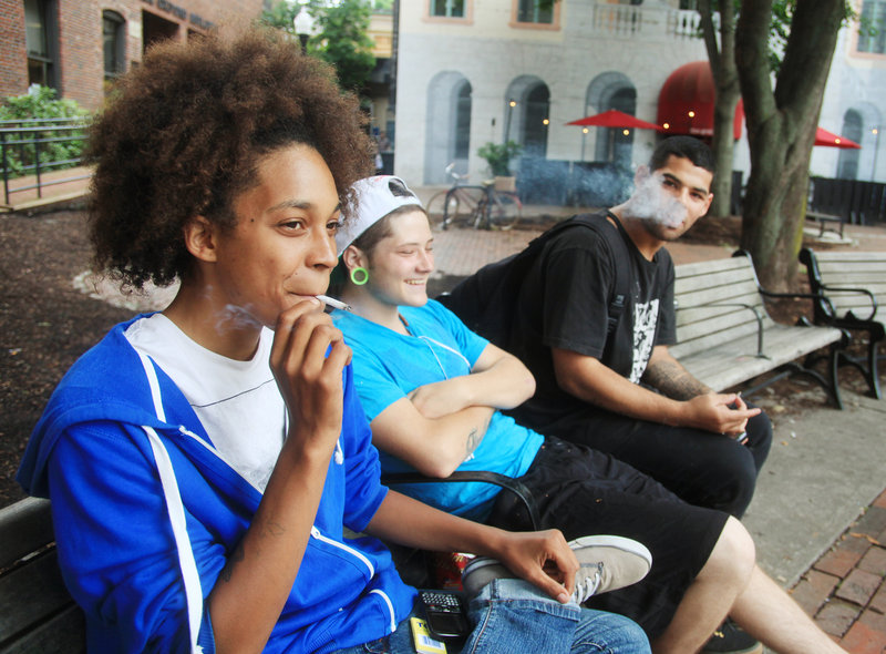 From left, Sierra Reed and Alex Hanks, both of Portland, and James Emmons of Windham smoke on a park bench in Tommy's Park in Portland on Monday afternoon, July 8, 2013. Reed says she hadn't even seen the sign posted about no smoking in public places.