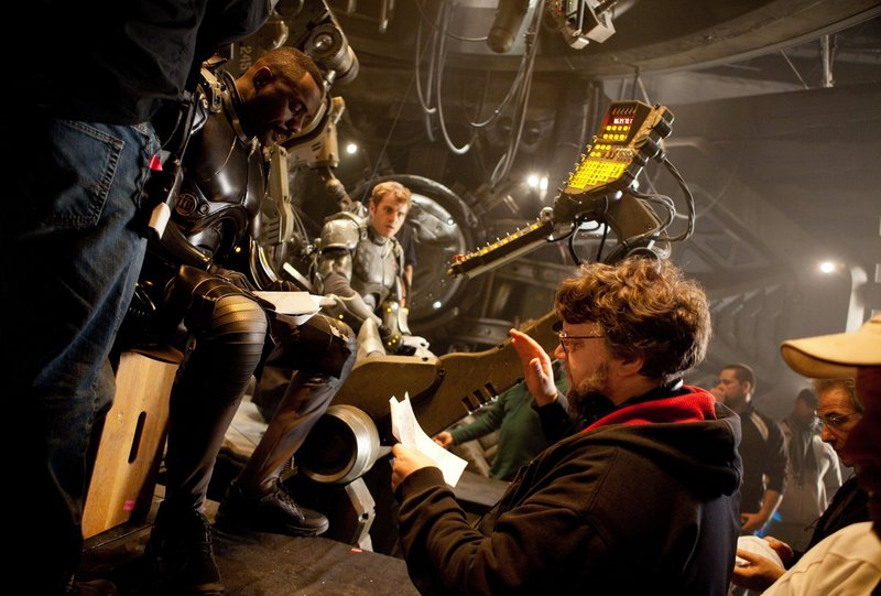 "Idris Elba, left, Rob Kazinksy and director Guillermo del Toro on the set of ""Pacific Rim."""