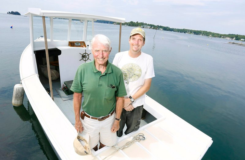 Eugene Story, left, and Eric Graves aboard their electric lobster boat July 8 in Boothbay Harbor.