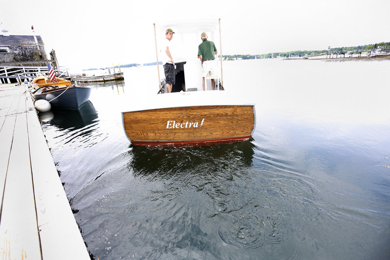 Eugene Story, owner of Maine Electric Boat Co., right, and Eric Graves, president of Boothbay Harbor Shipyard, leave the dock on their electric-powered lobster boat July 8 in Boothbay Harbor. Next month, they will install an 8-kilowatt, direct-current diesel generator.