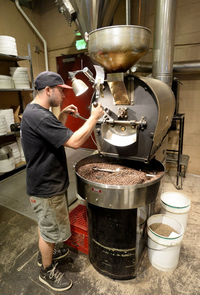 Asa Korsen roasts Peruvian coffee at Coffee By Design's Washington Avenue facility on Thursday, Co-owner Alan Spear said the company currently offers 35 different coffees and blends, excluding flavored coffee, from 17 countries.
