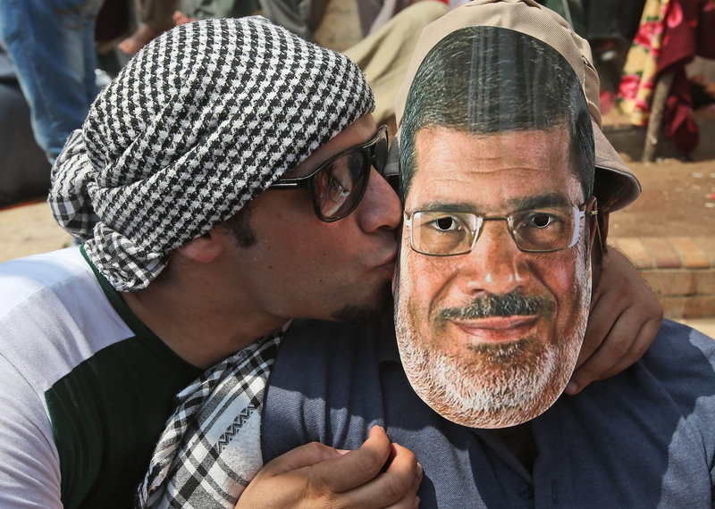 A supporter of Egypt's ousted President Mohammed Morsi, left, kisses a mask depicting Morsi worn by a fellow demonstrator Friday in Cairo. At the same time, supporters of Egypt's Muslim Brotherhood rallied in cities across Egypt.