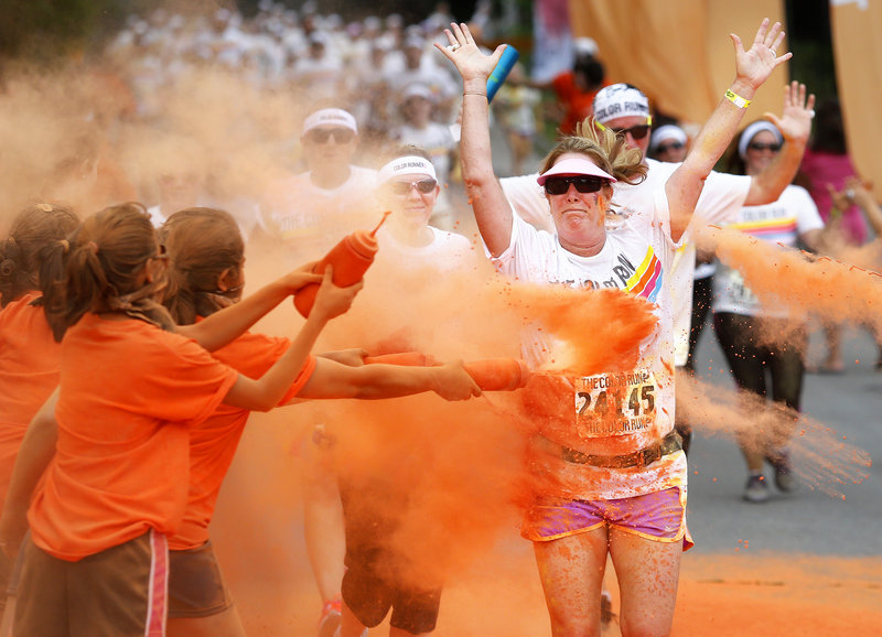 Participants are doused in orange-tinted cornstarch during The Color Run in South Portland earlier this month. It is one of several in Maine this year being put on by for-profit companies, reflecting a national trend. Some worry that the fun runs will compete for participants with traditional local road races.