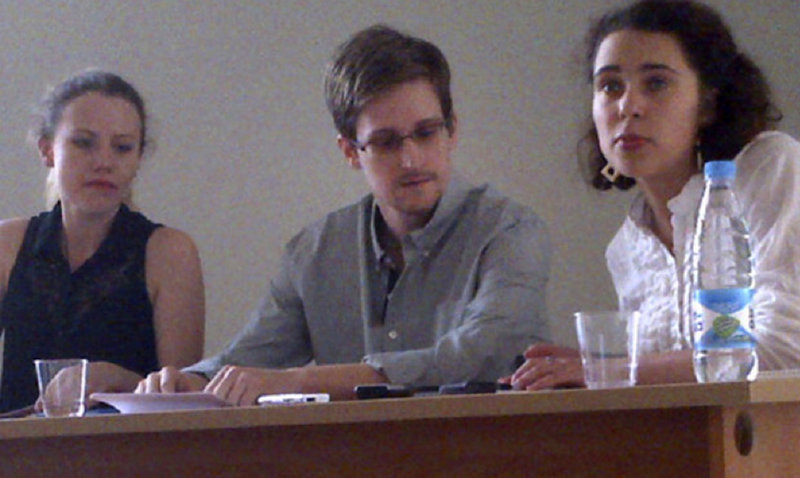 """Edward Snowden, center, holds a news conference at Moscow's Sheremetyevo Airport Friday with Sarah Harrison, left, of WikiLeaks. Snowden defended his disclosure of secret surveillance undertaken by the United States and said he has no regrets because """"it was the right thing to do."""" The woman at right was not identified."""