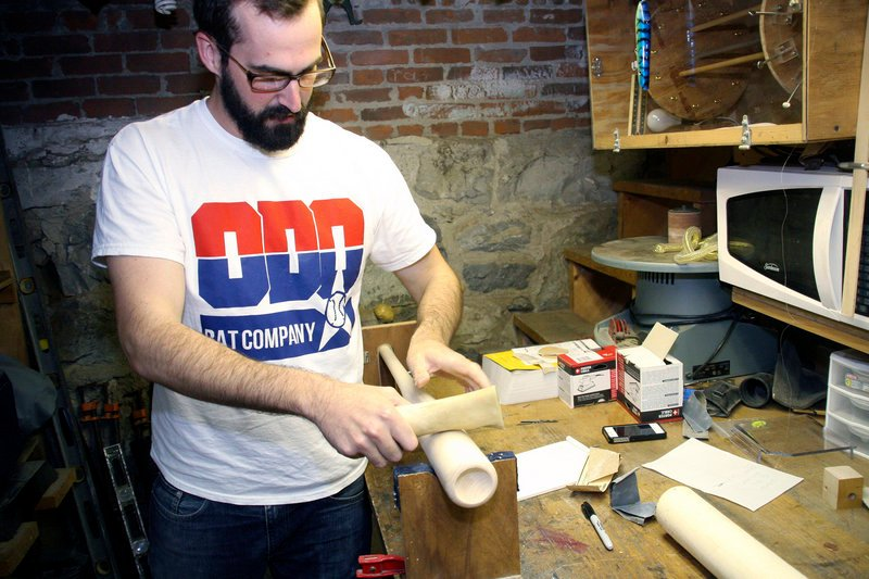 Casey O'Donnell uses a cow femur to harden and smooth one of the wooden bats being made in Pittsfield, Mass.