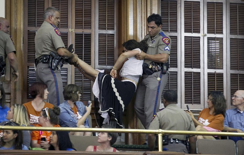 Police arrest a woman in the Senate Chamber at the Capitol in Austin, Texas, during the abortion debate Friday.