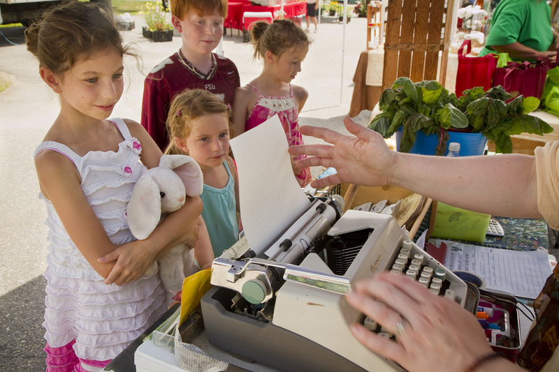 Abigail Kline, 9, of Destin, Fla., at left, watches with other children as organic farmer Holly Morrison of Pownal, loads up the typewriter to create a poem commissioned by the youngster at the Cumberland Farmer's Market on Saturday.