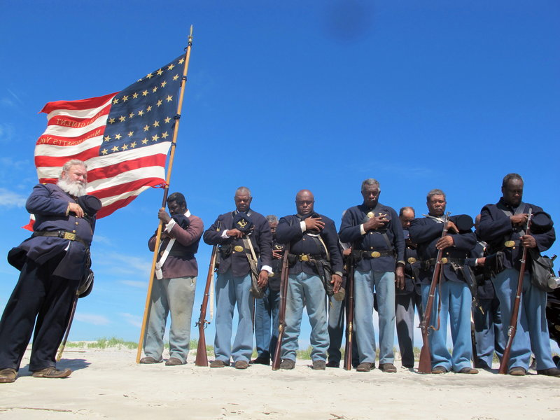"""Re-enactors pray on the beach on Morris Island in Charleston, S.C., in a ceremony honoring the 54th Massachusetts Volunteer Infantry, the black Union unit that attacked Confederate Battery Wagner, in a fight recounted in the film """"Glory."""""""