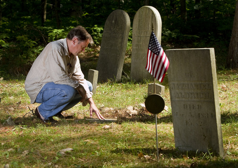 Film producer Frank Pote, who is undertaking a documentary about the Captain Greenfield Pote House, the oldest house in Freeport, examines a gravestone near the home Monday July 15, 2013.