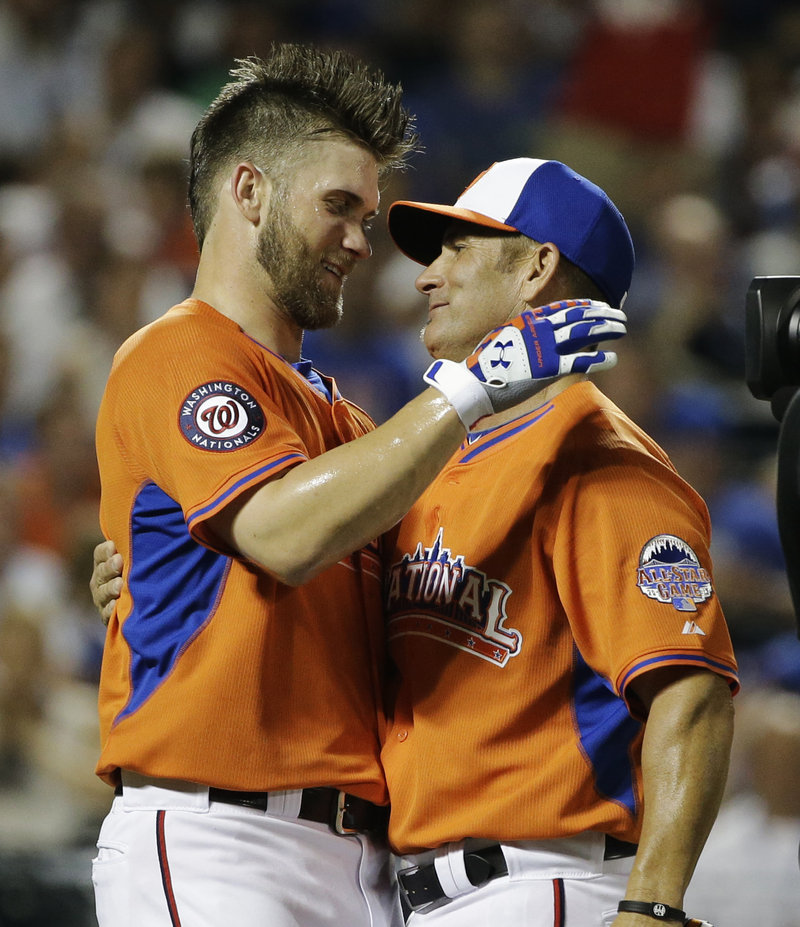 Bryce Harper, left, of the Washington Nationals, embraces his father, Ron, at the end of the third round of the All-Star baseball Home Run Derby. Harper finished second to Oakland's Yoenis Cespedes.