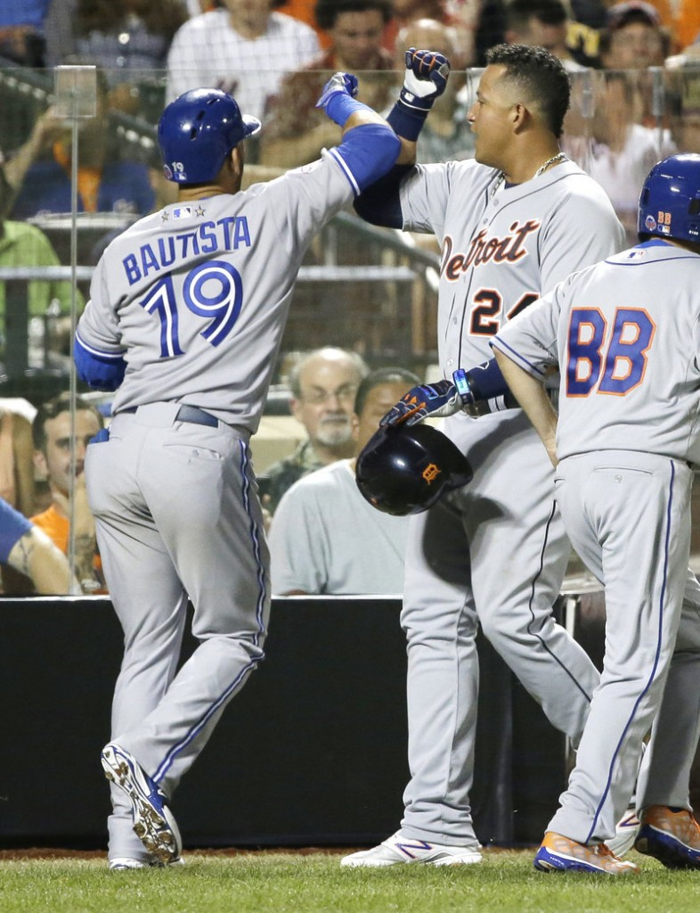 Miguel Cabrera of the Detroit Tigers is congratulated by Jose Bautista of the Toronto Blue Jays after scoring on Bautista's sacrifice fly during the fourth inning of the American League's 3-0 victory in the All-Star game at Citi Field in New York.