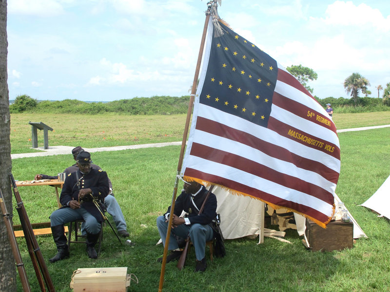Walter Sanderson of Upper Marlboro, Md., left, and Louis Carter of Richmond, Va., re-enactors portraying members of the 54th Massachusetts Volunteer Infantry, sit in an encampment at Fort Moultrie on Sullivans Island, S.C., on Thursday, July 18, 2013. The re-enactors gathered to commemorate the 150th anniversary of the famed Civil War attack by the 54th Massachusetts Volunteer Infantry in a fight commemorated in the film