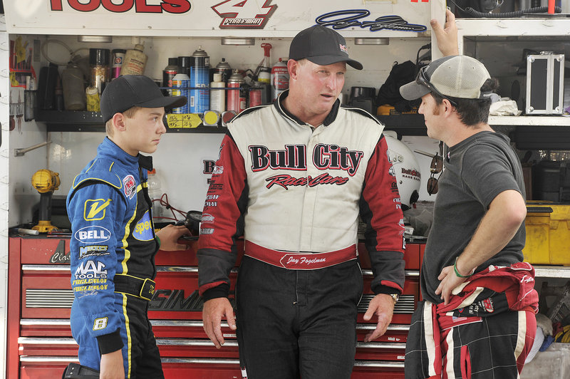 Jay Fogleman, center, and his son, 13-year-old Tate, discuss the day's practice runs with another team member at Oxford Plains Speedway in preparation for Sunday's TD Bank 250. Jay's father, 71-year-old Kent Fogleman, is a retired racer who will be in the stands.
