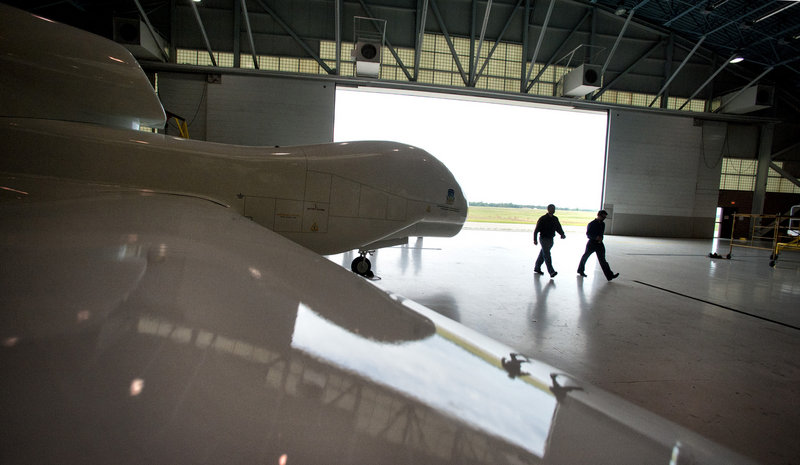 Two instructors pass a model of a Northrop Grumman Global Hawk at Northland Community and Technical College in Thief River Falls, Minn. The Air Force tried but failed to scuttle the Global Hawk program.