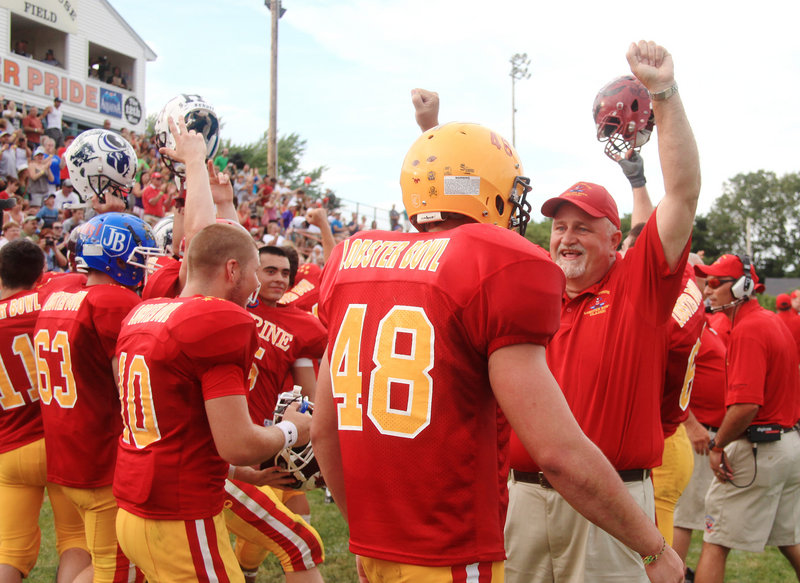 Bill County of Lewiston High, a coach for the East team, celebrates with his players Saturday as time runs out on a 25-13 victory against the West in the annual Lobster Bowl at Waterhouse Field in Biddeford. The West leads the series, 17-7.