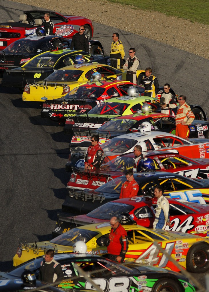 Drivers, with helmets propped atop their race cars, stand at attention just prior to the playing of the national anthem at the TD Bank 250 in Oxford.
