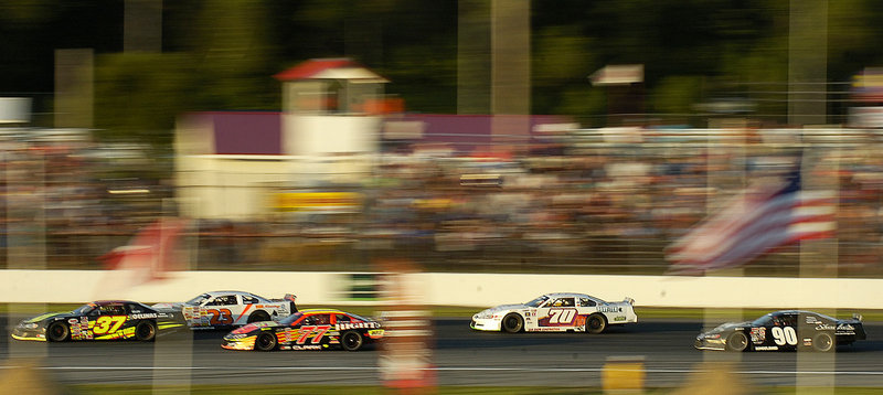 Race cars streak down the backstretch at Oxford Plains Speedway on Sunday, where Travis Benjamin of Morrill beat Berwick's Joey Doiron, the current PASS North points leader.