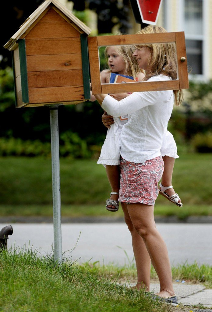Kristin Jordan and her daughter Ruby, 3, look over the selection of books in their Little Free Library at their Portland home.